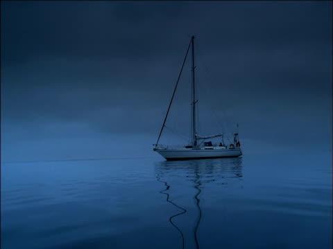 yacht floats on still ocean. - anker werfen stock-videos und b-roll-filmmaterial
