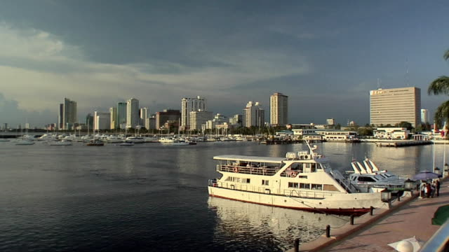 WS, Yacht in harbor, skyline of Malate district in distance, Manila, Philippines