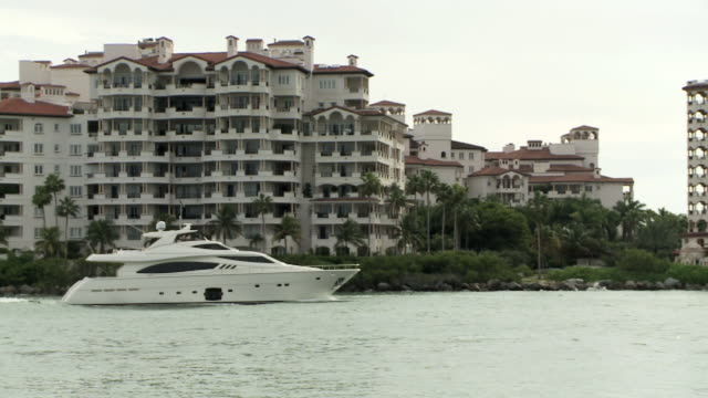 yacht motorboat moving across biscayne bay fisher island midrise condominiums apartments bg boating recreation wealth luxury - biscayne bay bildbanksvideor och videomaterial från bakom kulisserna