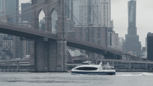 yacht moving on east river under brooklyn bridge - brooklyn bridge stock videos & royalty-free footage