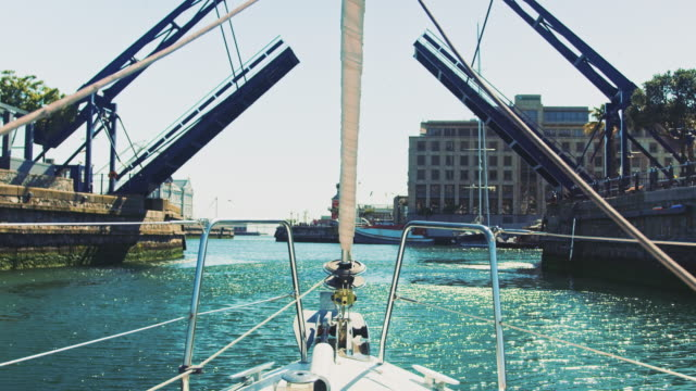 yacht moving towards harbor under drawbridge - telecamera traballante video stock e b–roll