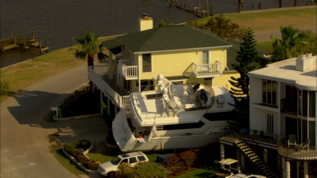 a yacht rests between two large houses in the aftermath of a hurricane. - wealth stock videos & royalty-free footage