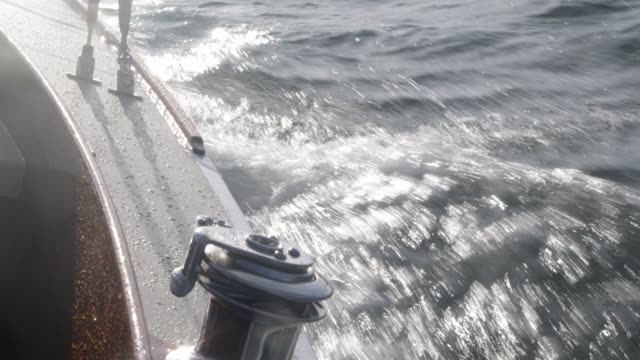vídeos de stock e filmes b-roll de yacht sailing at speed, close up of side deck. - moving past