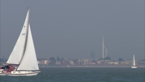 ms yacht sailing over water and  spinnaker tower in background / southampton, hampshire, united kingdom - smith tower stock-videos und b-roll-filmmaterial