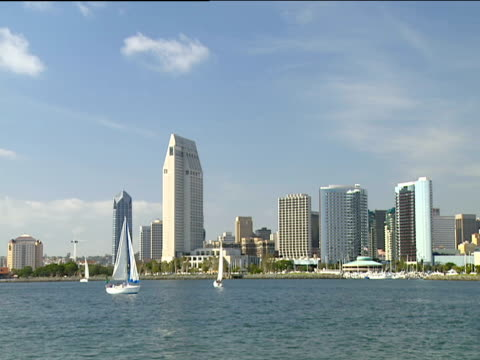 yacht sails from right to left in san diego marina skyscrapers in background under clear blue sky - san diego stock videos & royalty-free footage