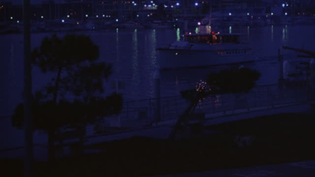 a yacht slowly cruises through a marina. - jachthafen stock-videos und b-roll-filmmaterial