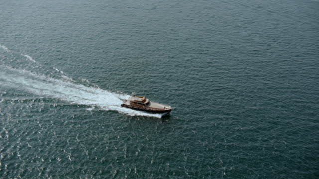 AERIAL Yacht traveling down the Bosphorus Strait and passing a ferry boat / Istanbul, Turkey