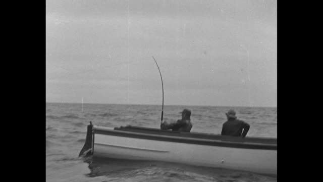 pov a yacht with attached skiff / smiling julian t crandall / hands on a very large fishing reel / vs crandall on small boat with large rod and reel... - fishing reel stock videos and b-roll footage