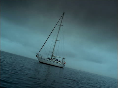 yacht with sails lowered floats on calm sea, south africa - tauwerk stock-videos und b-roll-filmmaterial