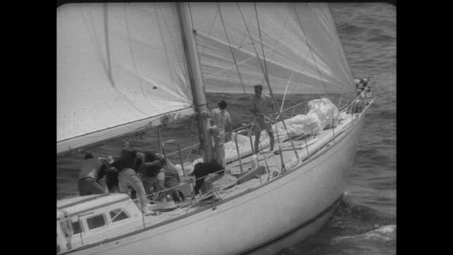 vídeos y material grabado en eventos de stock de yachts along both sides of the pier on the day of the bermuda newport yacht race / men climbing on board yacht / man securing rope on front of boat /... - sumar