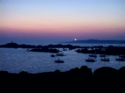 wa yachts anchored at lavezzi island at dusk with lighthouse flashing, france - anchored stock videos & royalty-free footage