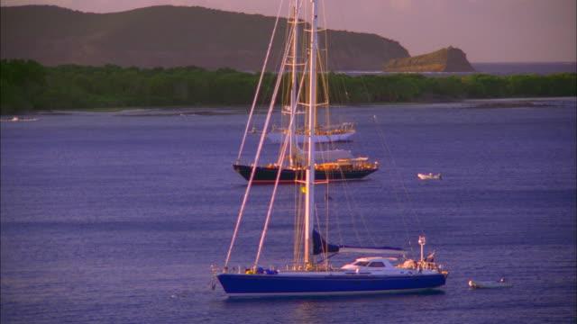 vídeos de stock e filmes b-roll de yachts moored at sunset, grenadines available in hd. - ancorado