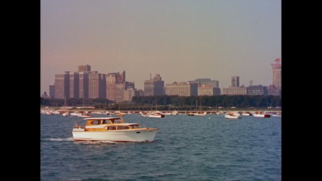 ws ts yachts moving on lakefront, cityscape of chicago behind / chicago, illinois, united states - 1960年点の映像素材/bロール