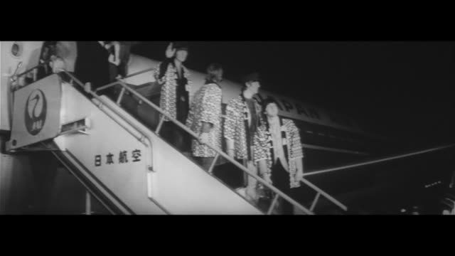 vídeos de stock e filmes b-roll de yah yah yah/29 june heavy security at haneda airport removing youths hiding in the toilets the beatles standing on the ramp heading to their hotel in... - the beatles