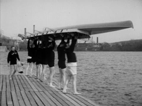 vídeos de stock, filmes e b-roll de yale varsity shell students carrying row boat, warren zimmerman taking notes, various crews rowing across housatonic river, coach w/ megaphone, boats... - universidade de yale
