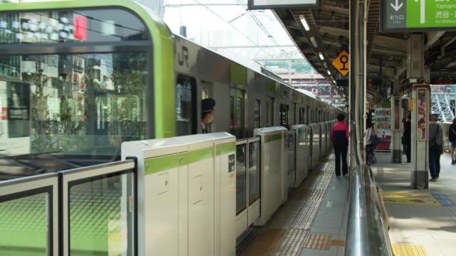 yamanote line train leaving harajuku station - underground station stock videos & royalty-free footage