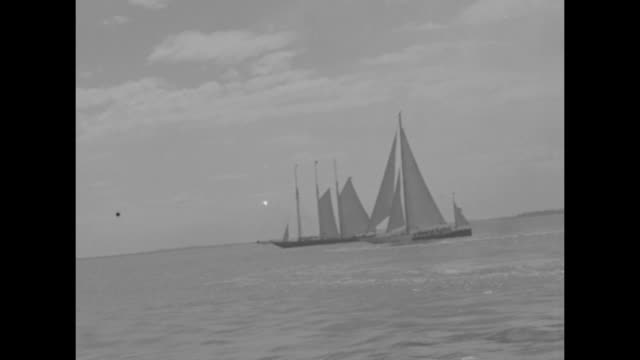 yankee commodore gerard lambert's yacht sailing to england from boston / crew on deck waving / tugboats leading yankee to sea / schooners at sea - massachusetts stock videos & royalty-free footage