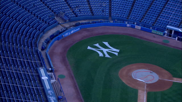 Yankee logo on empty field behind home plate passing 'Yankee Stadium' sign in front of stadium ZO to stadium New York Yankees Bronx Bombers Major...