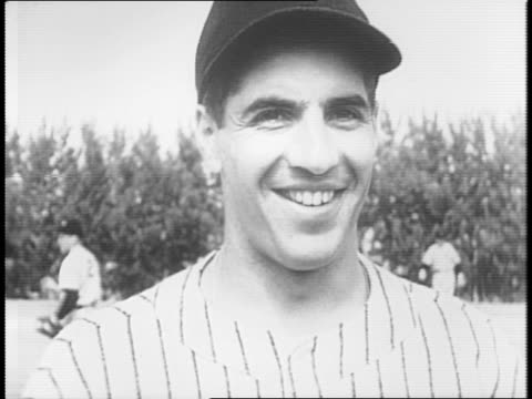 Yankees catcher Bill Dickey warms up on field / Rookie players smile for camera including Phil Rizzuto Tommy Holmes George Barley Johnny Sturm and...