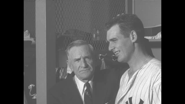 yankees manager charles casey stengel wearing a suit pats don larsen yankees pitcher on the head and says he's alright as he poses with larsen in the... - new york yankees stock-videos und b-roll-filmmaterial
