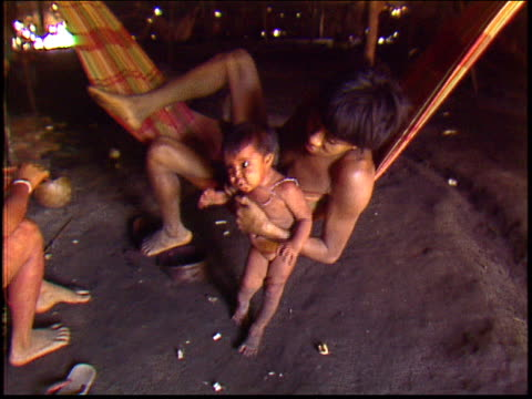 a yanomami child is picked up and passed across to its mother inside a traditional maloca dwelling - yanomami stock videos and b-roll footage