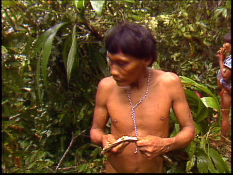 a yanomami indian man eats fruit in the amazon rainforest - yanomami stock videos and b-roll footage
