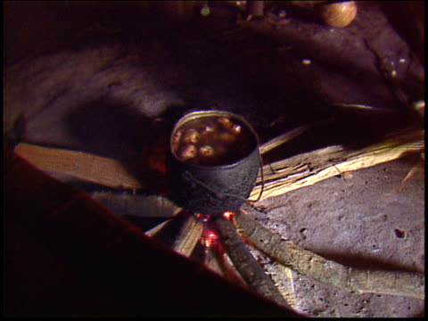 a yanomami indian man fans the fire underneath a cook pot inside a traditional maloca dwelling - yanomami stock videos and b-roll footage