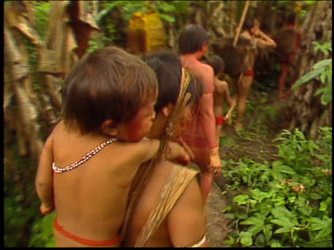 yanomami indians carry children through the amazon rainforest - yanomami stock videos and b-roll footage