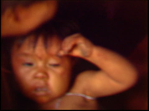 a yanomami mother and child share a hammock inside a traditional maloca dwelling - yanomami stock videos and b-roll footage
