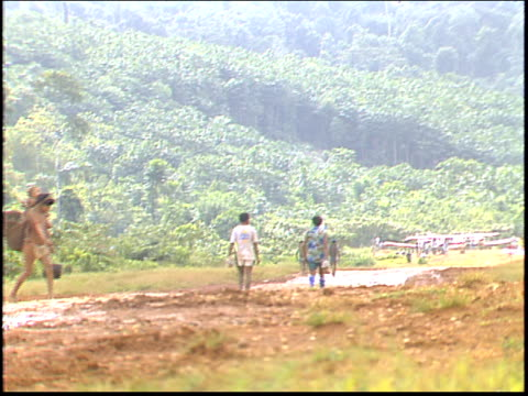 a yanomamo indian woman carries her child across a jungle runway in the amazon that services a nearby gold mine - yanomami stock videos and b-roll footage