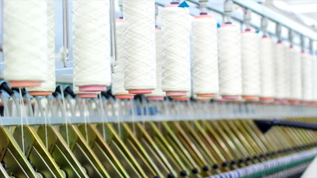 Yarn spools on spinning machine in a factory