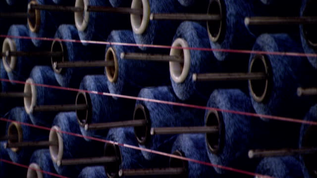 vidéos et rushes de yarn unwinds from large spools in a carpet manufacturing plant. - fil mercerie