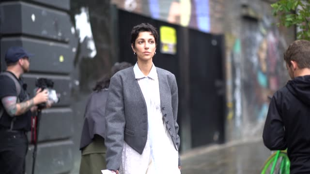 yasmin sewell wears a gray jacket, a white dress, black boots, a blue bag shaped as a cap hat, during london fashion week september 2019 on september... - gray jacket stock videos & royalty-free footage
