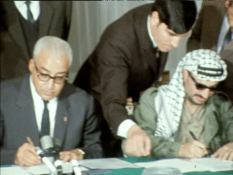 Yasser Arafat and King Hussein of Jordan signing peace treaty in Tunisian Embassy Oct 70