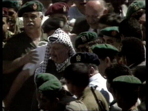 Yasser Arafat returns to Gaza GAZA STRIP Car towards and stops as Yasser Arafat out PAN RL as through crowd TMS Arafat bends down and kisses ground...