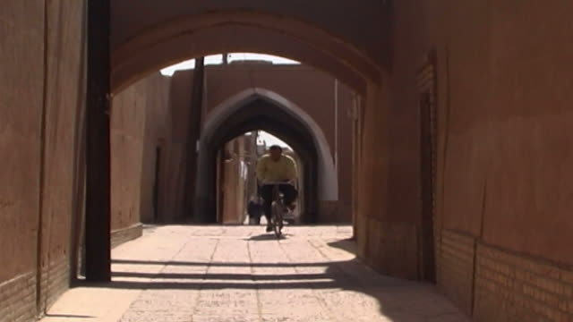 yazd general views. view of a man cycling in an alleyway in the city of yazd. - yazd province stock videos & royalty-free footage