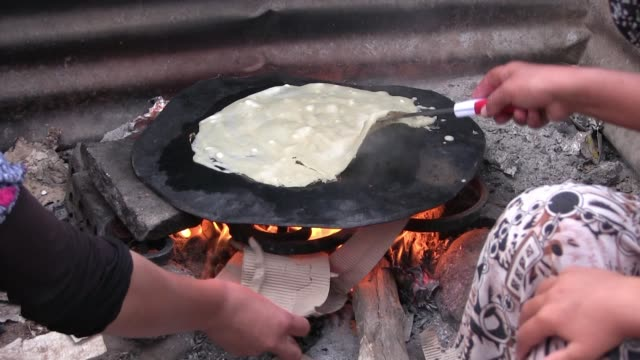 yazidi women bake iraqi flat bread at a refugee camp for displaced people from the minority yazidi sect which were driven from their homes in sinjar... - sinjar mountains stock videos & royalty-free footage
