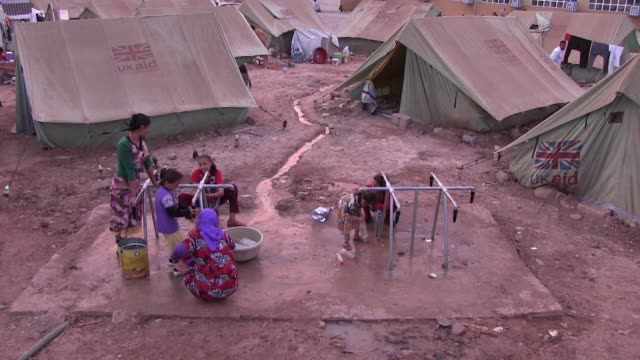 yazidi women fill drinking water in plastic jerrycans at a refugee camp for displaced people from the minority yazidi sect which were driven from... - sinjar mountains stock videos & royalty-free footage