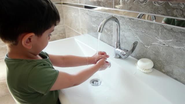bimbo di 3 anni si lava le mani con sapone in bagno - bagno domestico video stock e b–roll
