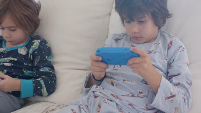 vídeos y material grabado en eventos de stock de 3 year old boy and his 7 year old brother using a console game - nativo digital