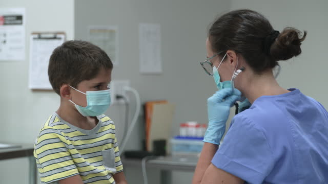 6 year old boy at doctors appointment wearing a protective face mask - fatcamera stock videos & royalty-free footage