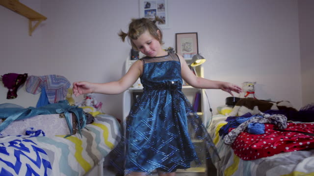 8 year old boy dances in his shiny blue dress and high heels.