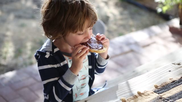 vídeos de stock e filmes b-roll de 4 year old boy eating chocolate spread on toast - lanche