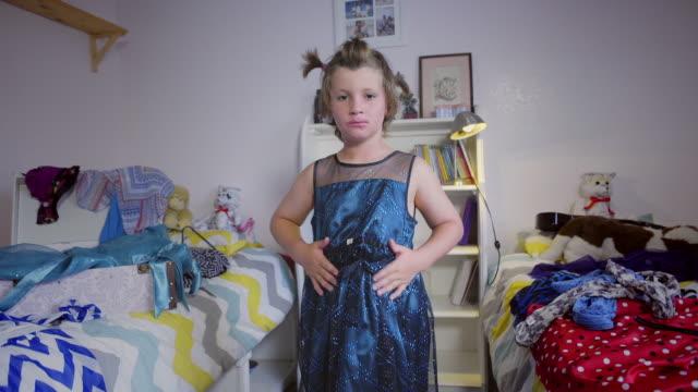 vidéos et rushes de 8 year old boy fluffs and ties a shiny blue dress - trans