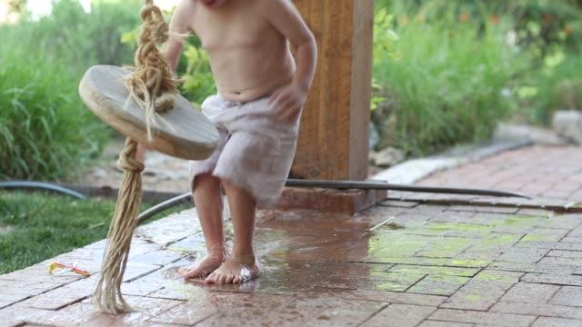 vídeos de stock, filmes e b-roll de 3 year old boy jumping in puddle - pátio