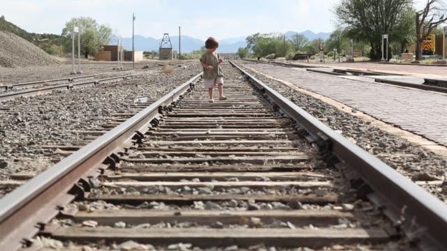 3 year old boy on rail road tracks