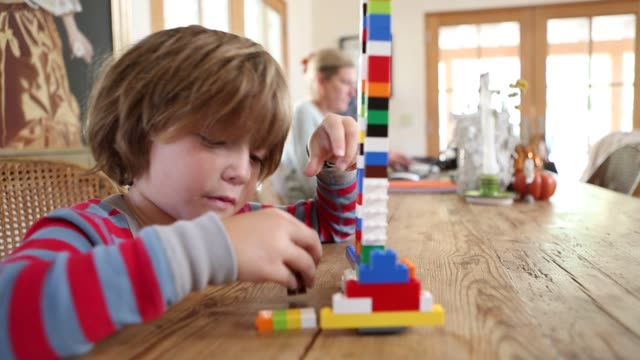 4 year old boy playing as his mother works - toy block stock videos and b-roll footage