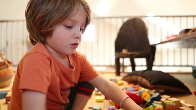 vídeos de stock, filmes e b-roll de 4 year old boy playing with wooden blocks - colocar a língua para fora
