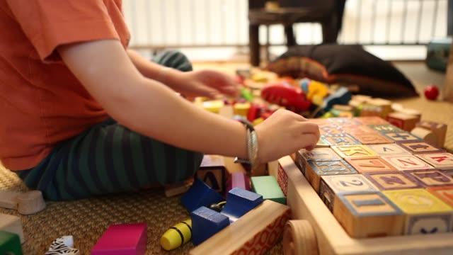 4 year old boy playing with wooden blocks - 胡坐点の映像素材/bロール