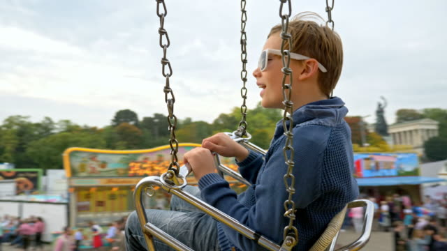 10 year old boy takes a chain swing carousel ride while visiting the 'Oide Wiesn' during Oktoberfest 2017 - blurred background